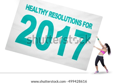 Healthy Indian woman pulling a big banner with text of healthy resolution for 2017, isolated on white background