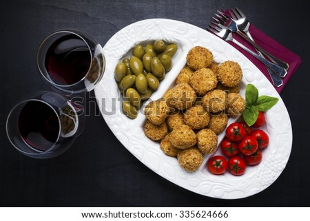 Healthy Italian Appetizer with Risotto Balls Arancini , green Olives , tomato and red WineSicilian homemade Snack - stock photo