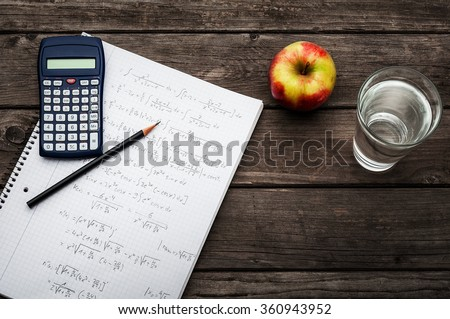 Healthy learning concept - handheld calculator and pencil over a sheet of paper with maths-formulas, an apple and a glass fresh water on a dark wooden desk - stock photo