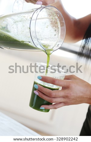 Healthy life. Girl making a drink from spinach