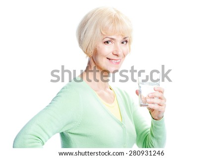 Healthy lifestyle. Attractive middle aged woman holding glass of water and looking at camera. Isolated on white. - stock photo