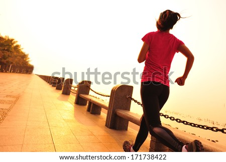 healthy lifestyle beautiful asian woman running at seaside under sunrise in the morning - stock photo