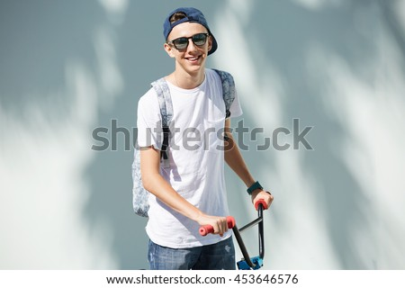 Healthy lifestyle concept. Cute teenage boy in sunglasses, carrying backpack, looking and smiling at the camera, holding his bicycle by the handlebar, having rest during his ride in the city center - stock photo