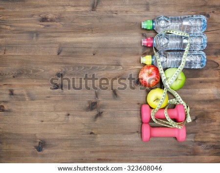 Healthy lifestyle concept. three colored Apples measuring tape dumbbells and sport  water bottles on  wooden table  - stock photo