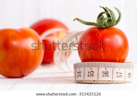 Healthy lifestyle concept with measuring tape and red tomato fruits - stock photo