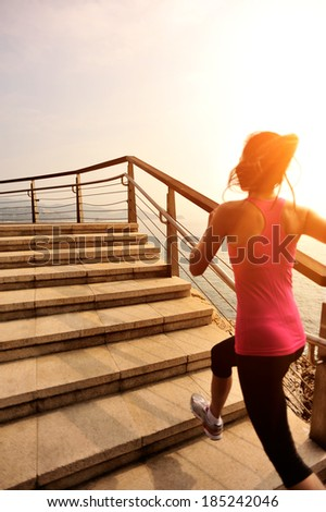 healthy lifestyle fitness sports woman running on seaside stone stairs  - stock photo