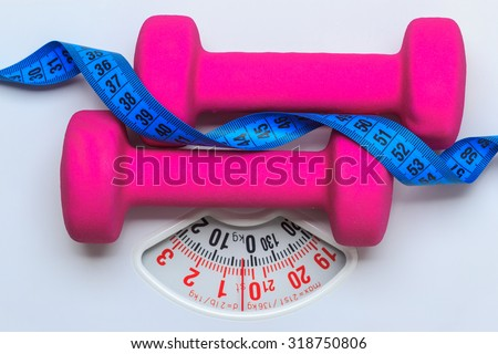 healthy lifestyle fitness weight control concept. Closeup pink dumbbells with blue measuring tape on white scales - stock photo