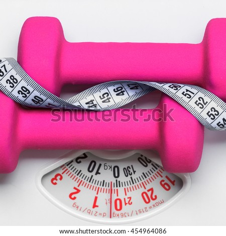 healthy lifestyle fitness weight control concept. Closeup pink dumbbells with measuring tape on white scales - stock photo