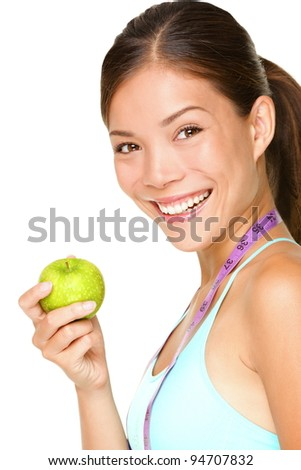 Healthy lifestyle. Fitness woman eating apple wearing measuring tape. Fit sporty multicultural Asian / Caucasian female fitness woman isolated on white background. - stock photo