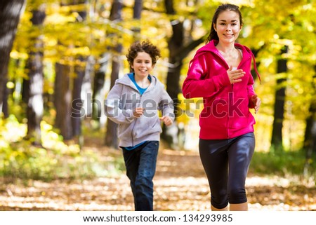 Healthy lifestyle - girl and boy jumping, running outdoor