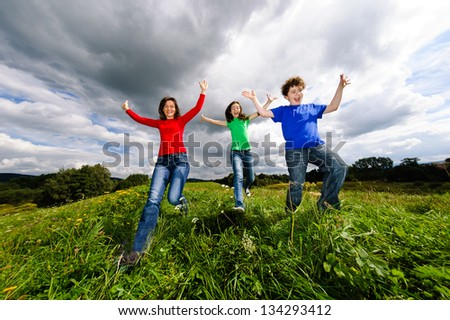Healthy lifestyle - mother and kids running, jumping outdoor