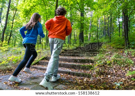 Healthy lifestyle - teenage girl and boy running, jumping outdoor  - stock photo