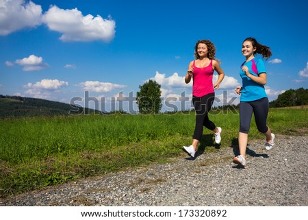 Healthy lifestyle - two women running, jumping outdoor  - stock photo