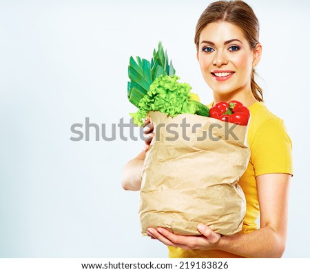 healthy lifestyle with green vegan food. young woman hold shopping bag with vegetables. - stock photo
