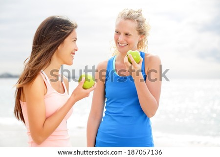 Healthy lifestyle women eating apple after running. Two beautiful girlfriends talking enjoying fruit after jogging training on beach. Caucasian woman and Asian woman in their 20s smiling happy. - stock photo