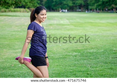 healthy lifestyle - Young adult happy asian woman do yoga in green grass field park to lose weight, standing one leg