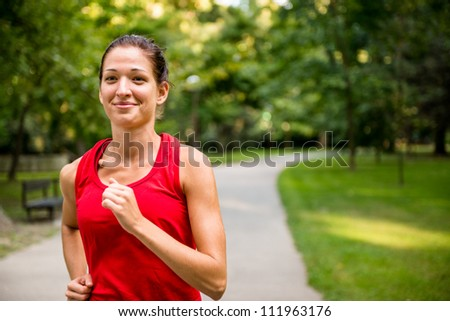 Healthy lifestyle - young beautiful woman jogging in nature - stock photo