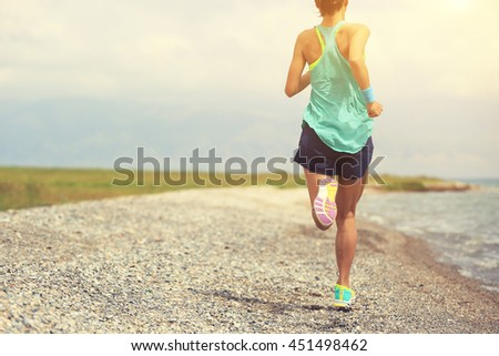 healthy lifestyle young woman runner running on seaside road