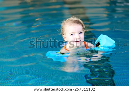 Healthy little child, blonde active toddler girl swimming in the pool learning to float using armbands  - stock photo
