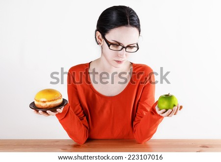 Healthy living concept: choosing between doughnut symbolizing unhealthy food and green apple symbolizing healthy food - stock photo