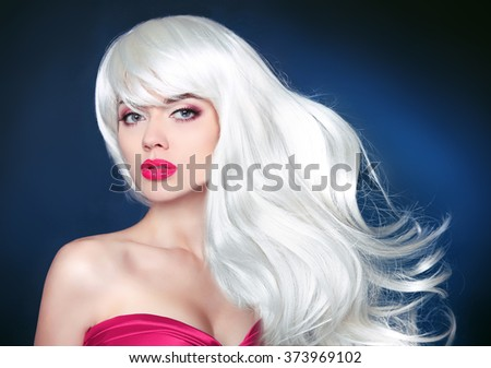 Healthy long Hair. Beautiful blond girl with long wavy hairstyle. Beauty woman portrait with bright makeup. Isolated on dark studio background. - stock photo