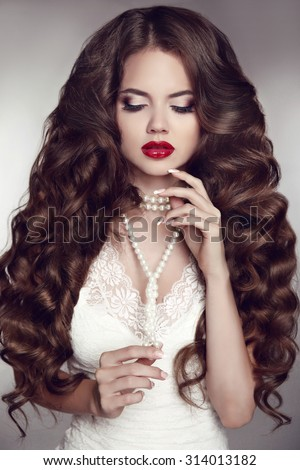 Healthy long hair. Girl makeup. Beautiful Brunette. Red Lips. Pearl necklace jewelry. Beauty Model Woman. Wavy Hairstyle.