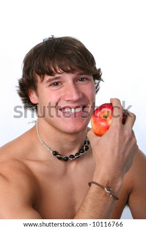 healthy looking young man holding apple on gray background
