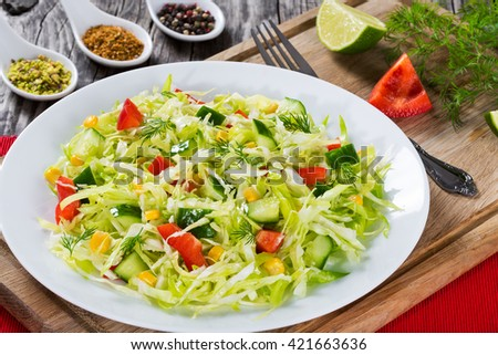 Healthy low calories spring cabbage salad with bell pepper, corn and dill, close-up