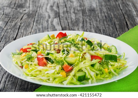healthy low calories spring cabbage salad with bell pepper, corn, cucumber and dill, on a white dish, simply and easy recipe, close-up, top view