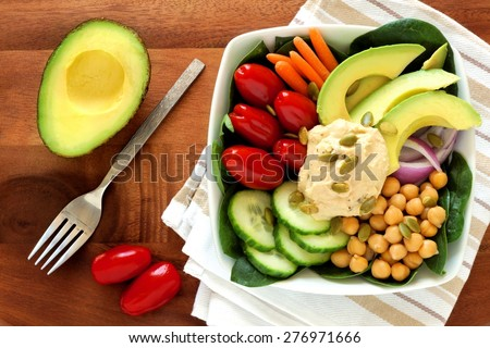 Healthy lunch bowl with avocado, hummus and fresh vegetables, overhead scene on wooden table - stock photo