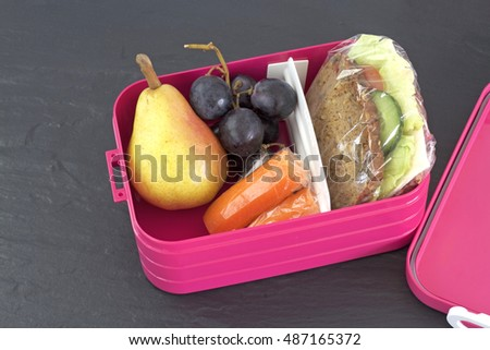 Healthy lunch box, cheese sandwich, pear, carrots and grapes