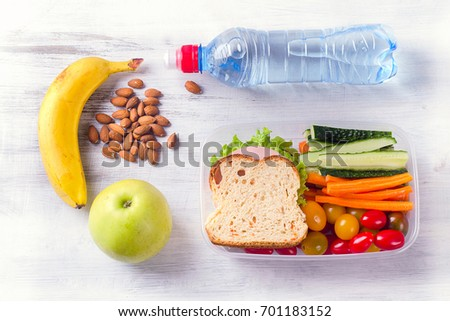 Healthy lunch box with sandwich and fresh vegetables, bottle of water. Healthy eating concept. Top view
