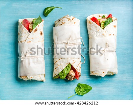 Healthy lunch snack. Tortilla wraps with grilled chicken fillet and fresh vegetables on blue painted wooden background. Top view - stock photo