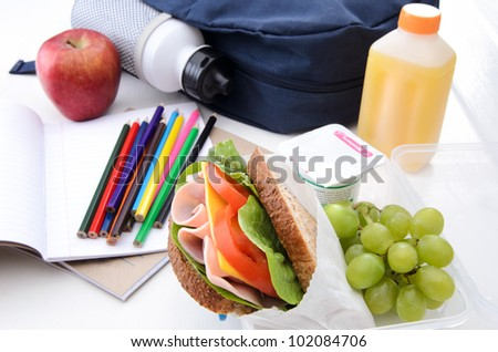 Healthy lunchbox with wholemeal ham sandwich, fruit, yogurt and orange juice - stock photo