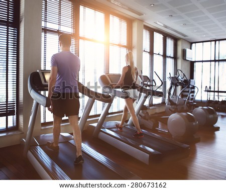 Healthy man and woman running on a treadmill in a gym. Sport and health concept - stock photo