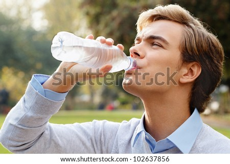 Healthy man drinking water outdoors - stock photo