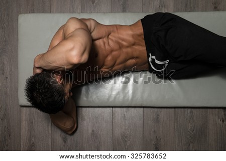 Healthy Man Exercising Abdominals On Foor - stock photo