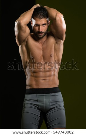 Healthy Man Standing Strong In The Gym And Flexing Muscles - Muscular Athletic Bodybuilder Fitness Model Posing After Exercises