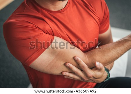 healthy man stretching shoulder before gym workout. Fitness strong male athlete. Young male fit exercising. - stock photo