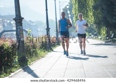 healthy mature couple jogging in the city  at early morning with sunrise in background - stock photo