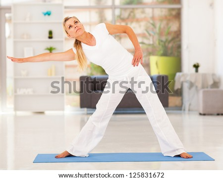 healthy mature woman doing exercise at home - stock photo