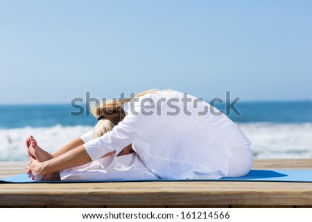 healthy mid age woman stretching outdoors