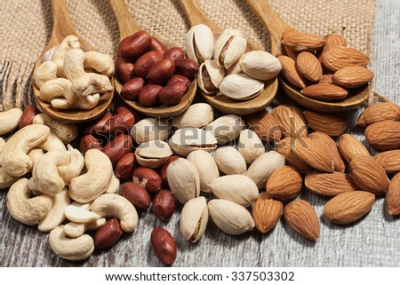 Healthy mix nuts on wooden background. Almonds, hazelnuts, cashews, peanuts