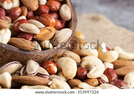 Healthy mix nuts on wooden background. Almonds, hazelnuts, cashews, peanuts, brazilian nuts - stock photo
