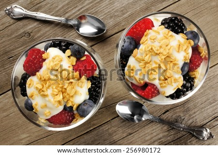 Healthy mixed berry, granola and yogurt parfaits, downward view on wood - stock photo