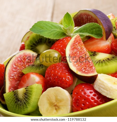 Healthy mixed fruit salad on the kitchen table - stock photo