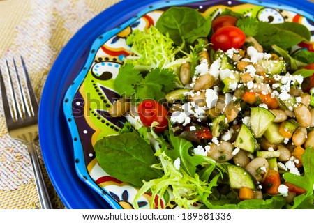 Healthy mixed green salad with white beans, zucchini, bell pepper, tomatoes sprinkled with crumbled cheese - stock photo