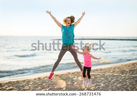 Healthy mother and baby girl jumping on beach in the evening - stock photo