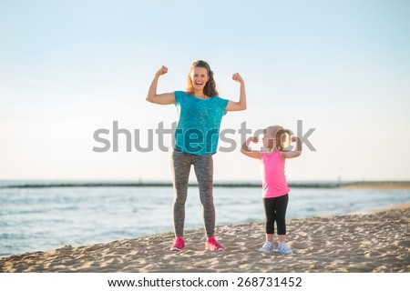 Healthy mother and baby girl showing biceps on beach - stock photo