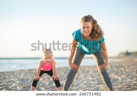 Healthy mother and baby girl workout on beach in the evening - stock photo